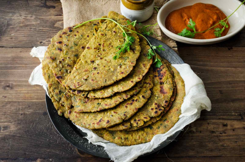 Bajra Aloo Roti is prepared with a mix of bajra flour, mashed potatoes, ginger garlic paste, coriander leaves, garam masala. It is served hot with white butter with raita as accompaniments. It tastes heavenly and just melts in the mouth.