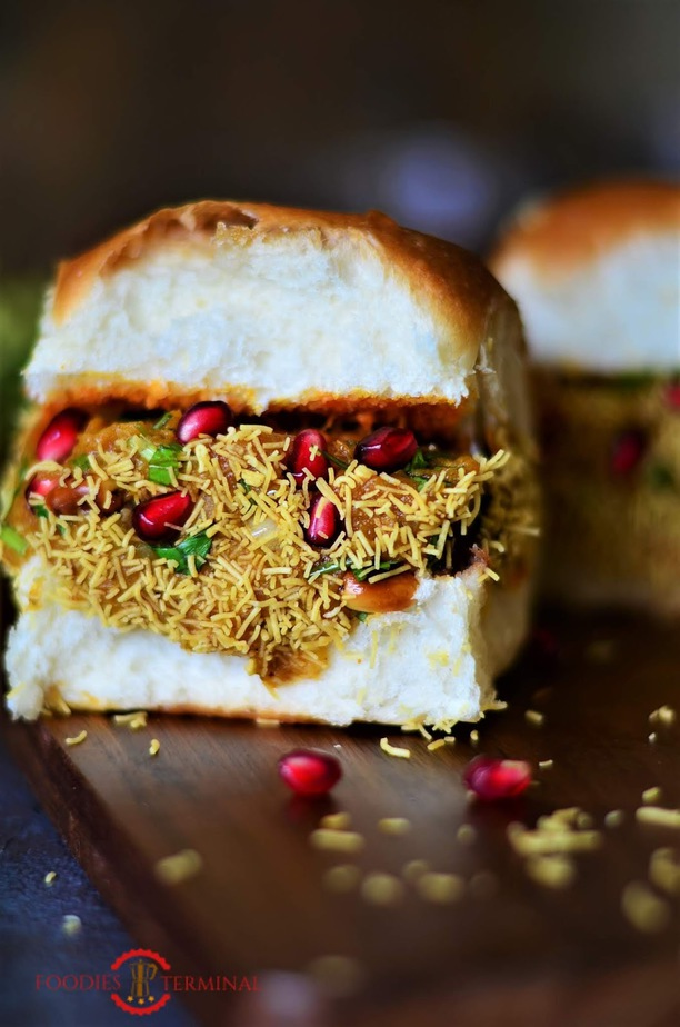 "Dabeli, Kutch dabeli or double roti is a popular snack food originating in the Kutchof Gujarat. Dabeli literally means ""pressed"" in Gujarati.It is made with mixing boiled potatoes with a special masala and served with chutney, pomegranate and roasted peanuts."