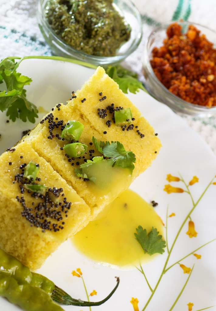 haman is a food common in the Gujarat , made from soaked and freshly ground chana dal .The final touch to the soft and fluffy khaman is added with a garnishing of sesame seeds, mustard seeds, coriander leaves. It is a variant of Dhokla and has a lighter colour.